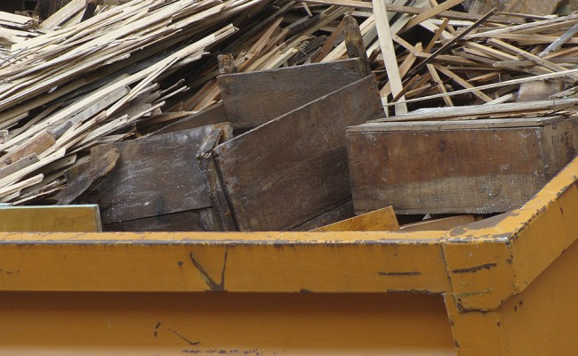 metal orange container filled with wood timber rubble